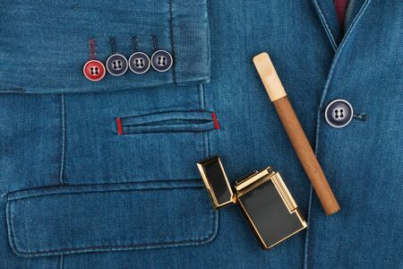 Cigar and a lighter lie on a denim jacket. Fashion background. Top view 스톡 콘텐츠