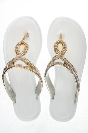 Glamorous white flip flops, sandals decorated with rhinestones on a white background. Top view.