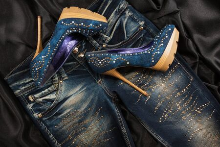 Luxurious womens denim shoes in rhinestones and jeans in rhinestones on a black silk. Fashion background. Top view