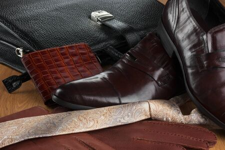 Classic brown shoes, tie, gloves and briefcase on the wooden parquet. Close-up. Fashion background Stock Photo