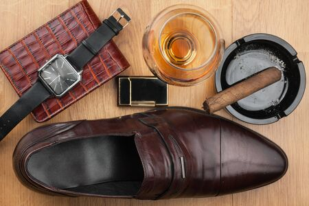 Men accessories. Brown elegant shoes, wallet, alcohol and cigar on wooden table. Top view.