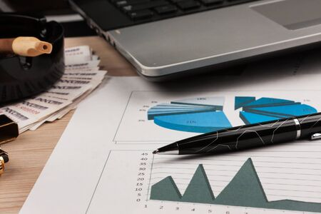 Pen and financial charts on the background of a laptop and cigar. Desktop, business background