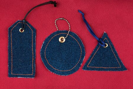 Set of denim price tags lying on red silk. Top view. Fashion and business
