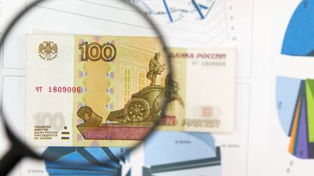 Magnifying glass and money - business background. Hundred ruble bill under a magnifying glass is being inspected. Conceptual photo