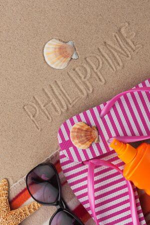 Word PHILIPPINE written in sand with beach accessories