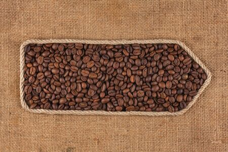 Symbolic pointer made of rope with coffee beans lying on a burlap. Top view