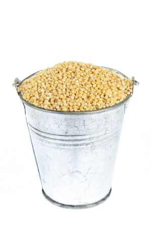 Full bucket of millet grains on a white background. With place for text.