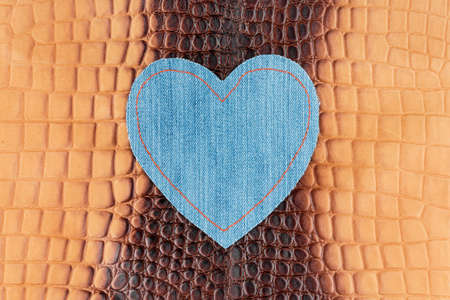 Blue denim heart lies on the brown crocodile skin. View from above Foto de archivo