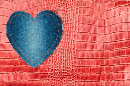 Blue denim heart lies on the red crocodile skin. View from above