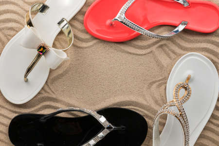 Sandals decorated with rhinestones on the sand of the beach. Copy space. Top view