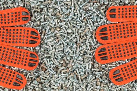 Work gloves lies on galvanized screws. Top view