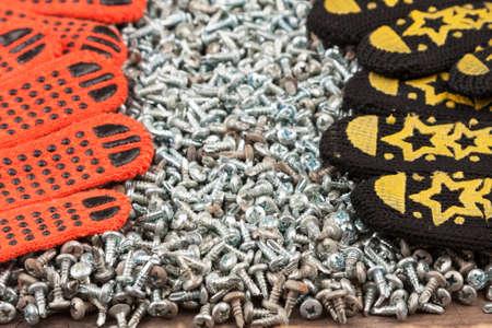 Work gloves lies on galvanized screws. Close-up