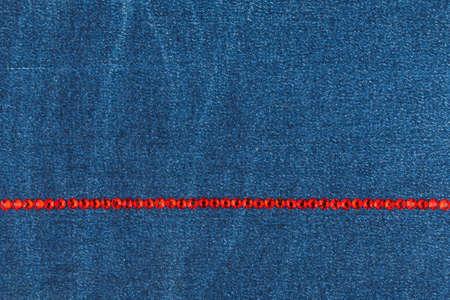Luxury fashionable background. Line of red rhinestones on denim. Copy space