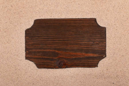 Wooden board with place for text on the sand. Top view. Copy space