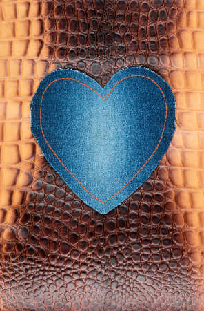 Blue denim heart lies on the brown crocodile skin. View from above Banco de Imagens