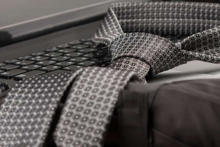 Close-up, tie lies on the laptop keyboard. Fashion background Banco de Imagens