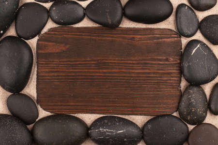 Frame made of black stones and a board on the sand. Top view. Copy space