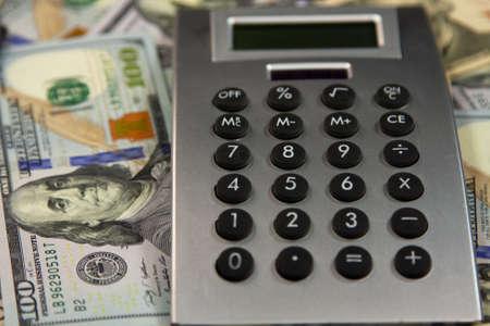 Calculator lies on the dollars. Close-up Banco de Imagens