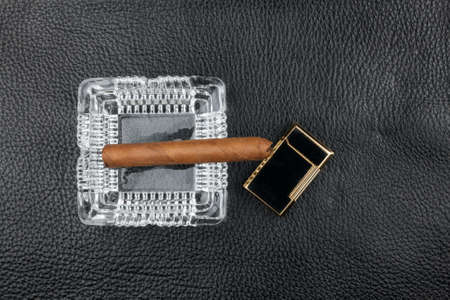 Ashtray, cigar and lighter lie on black natural leather. Top view