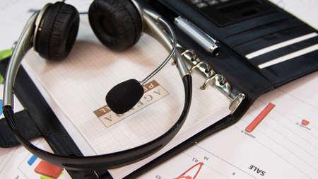 Agenda and headset close-up. Business background. Service desk Banco de Imagens