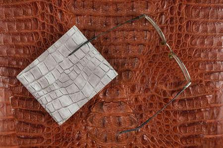 Male gray purse and glasses lying on crocodile skin. Top view Banco de Imagens
