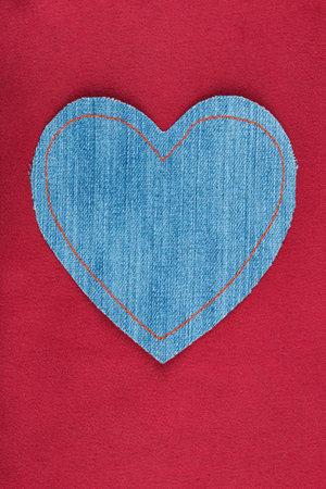 Denim heart with orange threads lies on red silk. Top view Banco de Imagens