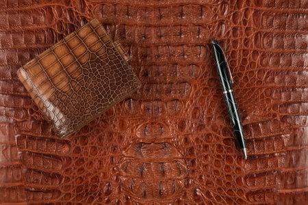 Male brown purse and pen lying on crocodile skin. Top view Banco de Imagens