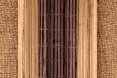 Two bamboo mat with curled edges lie on sacking. Top view Banco de Imagens
