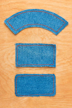 Price tags made of denim lying on wooden background. Top view