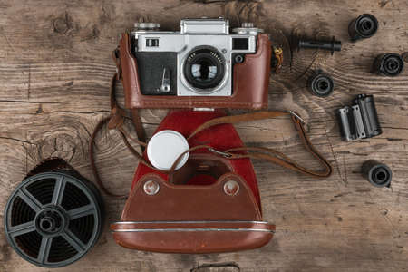 Retro camera in a brown leather case lies on a wooden table. Top view. Nostalgia Banco de Imagens