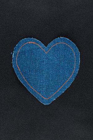 Denim heart with orange threads lies on black silk. Top view