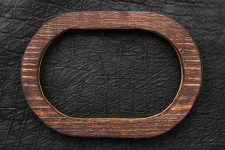 Oval wooden frame made of wood lies on black genuine leather. Top view. Sign, panel.