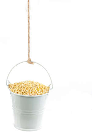 A full bucket of millet grains hanging from a rope. White background Archivio Fotografico - 164523875