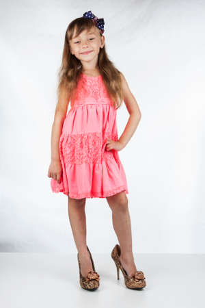 Cute little girl in high-heeled shoes posing on a white background. Fashion portrait of girl child.