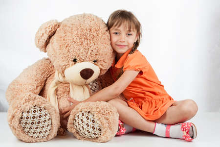 Cute little girl playing with her friend big fur bear. Baby girl hugging her teddy bear Stock Photo