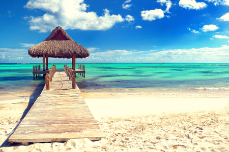 cana: Tropical white sandy beach. Palm leaf roofed wooden pier with gazebo on the beach. Punta Cana, Dominican Republic