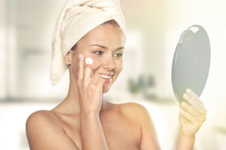 Beautiful , young woman wrapped in towel spreading cream on her face, shot on white background, Stock Photo