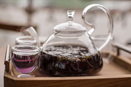Purple floral herbal tea is poured from the brewer into the cup. Фото со стока