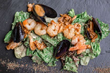 Seafood salad. Warm salad with leaves, shrimp, mussels and sause.