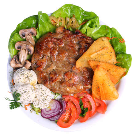 Hamburger on a platter with cheese, tomatoes, mushrooms, onions and lettuce, top angle