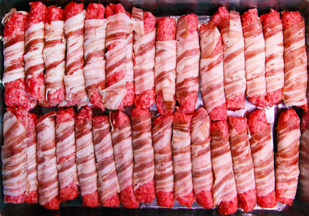 Rolled minced meat with bacon, arranged in series