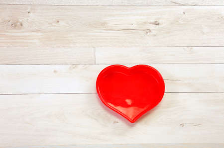 Red hart frame on a wooden background