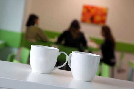 Two cups in the foreground and three girls Standard-Bild - 147659355