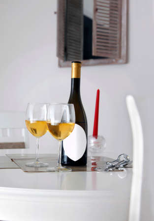 Bottle of wine with white label for caption, opener, two glasses of white wine on table and window in background