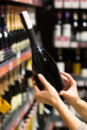 female hands holding a bottle of alcohol in the supermarket Standard-Bild