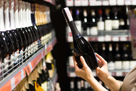 female hands holding a bottle of alcohol in the supermarket Stok Fotoğraf