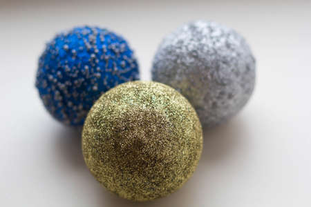 three multicolored christmas balls on a white background close-up.