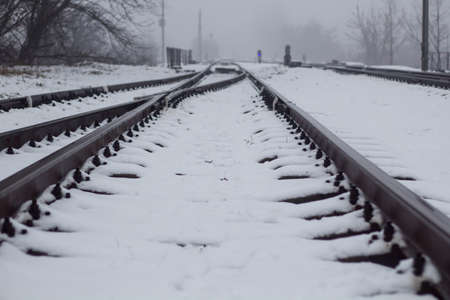 Gloomy railroad in the winter time of the year with snow.