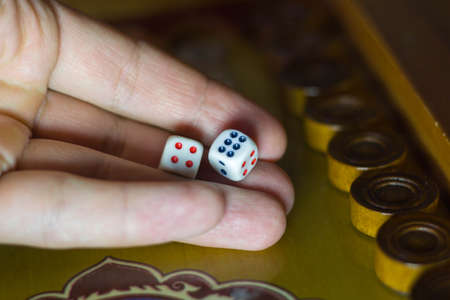 male hand holds dice in the game of backgammon.