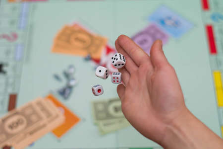 female hand throws dice in a board game close up.